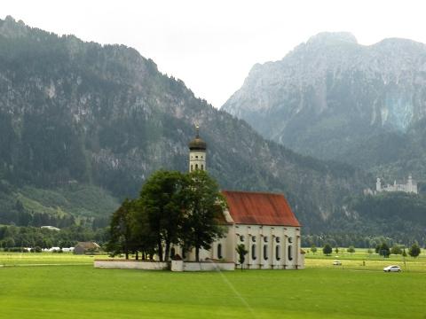 バス車窓から見えてきた聖コロマン教会とその向こうのノイシュヴァンシュタイン城